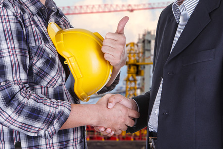 businessman shake hands with engineeringin construction site