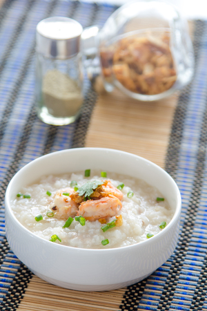 chinese meal: rice porridge with shrimp, squid on white table