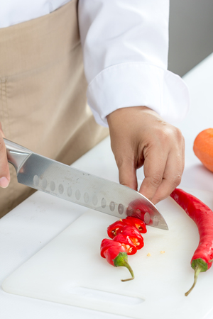 peper: chef slicing chili peper for cooking Stock Photo
