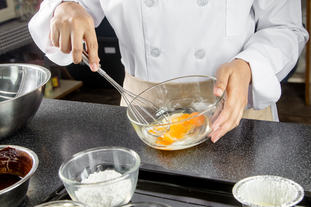 chef: cocinero bate los huevos en un recipiente para hacer la torta de chocolate