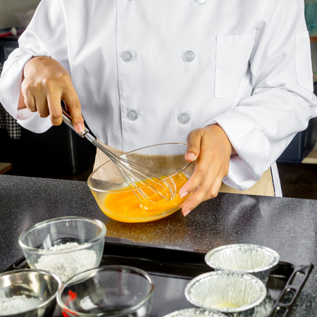 chef beating eggs in a bowl  to make chocolate cake