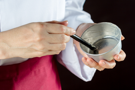 smearing: Chef using pastry brush smearing butter in pastry molds