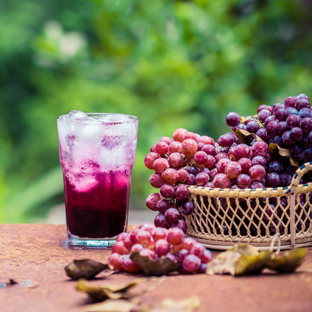 Red grape fruits and grape juice on wooden Stock Photo