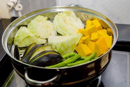 steaming: Pumpkin, cabbage, beans, eggplant in steaming pot Stock Photo