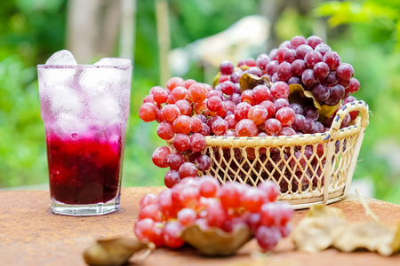 Red grape fruits and grape juice on wooden