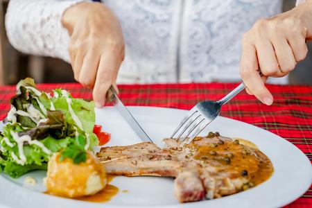 medium close up: women eating Pork chop steak in steak shop