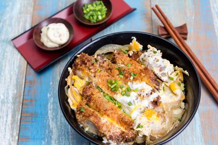 Japanese breaded deep fried pork with egg name is Katsudon in black plate Imagens