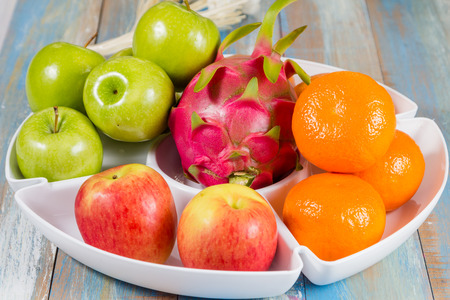 apple orange: rad apple, green apple, orange and dragon fruit in white tray in white tray Stock Photo