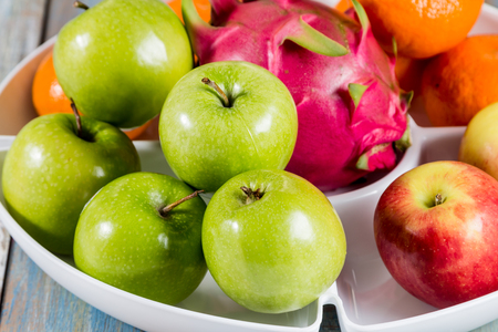 rad: rad apple, green apple, orange and dragon fruit in white tray in white tray Stock Photo