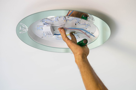 Hand Electrician Fixing Light On Ceiling Stock Photo