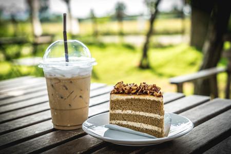 Scheibe Kaffeekuchen mit Mandelnuss und Buttercreme und Eiskaffee