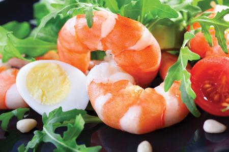 rukola: Salad of king prawns and rukola in a  black plate