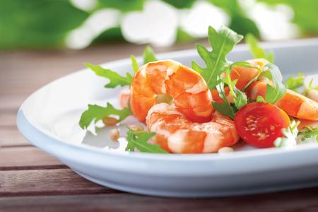 rukola: Salad of king prawns and rukola in a white plate