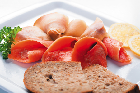 Mix of red and white pieces of salted fish on a white plate Stock Photo