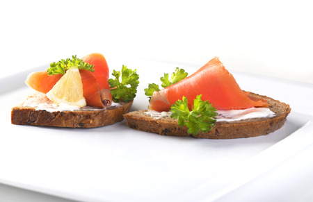 Two sandwiches with smoked salmon, sauce and parsley on a white background