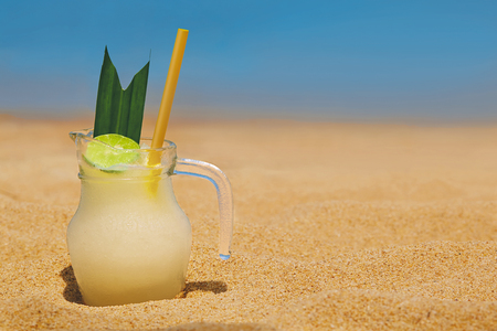 lemonade in the sand on sea background