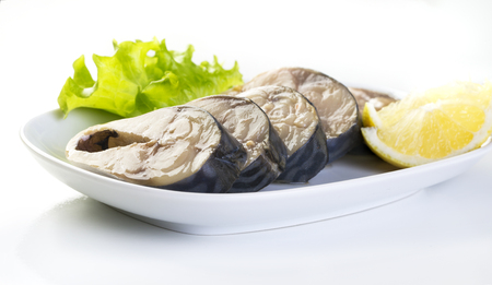 Pieces of mackerel and lemon on a white plate on a white background Banco de Imagens