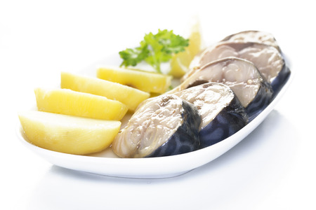 Pieces of mackerel and potatoes in a white plate on a white background