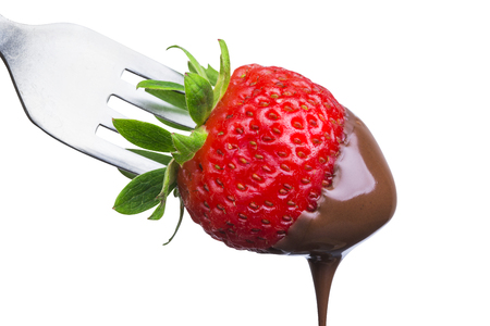 Fondue strawberry soaked in hot black chocolate on a fork isolated on white background