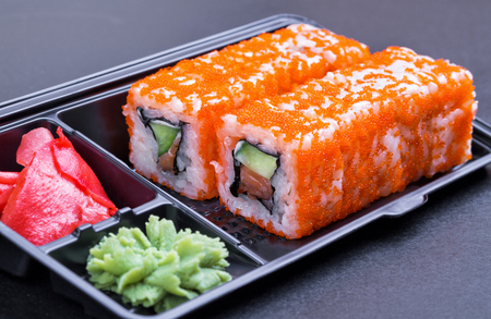 Set of California rolls in a black take away container on a black background side view