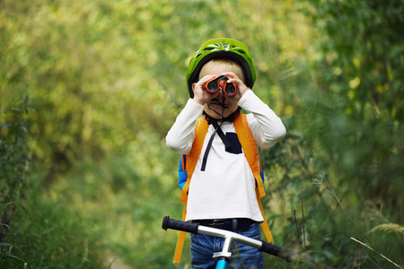 The little boy young researcher exploring with binoculars and backpack environment in the green forest on a sunny day Standard-Bild