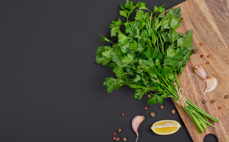 Bunches of fresh parsley bandaged with a rope with a bow, a mix of peppers in garlic on a black board