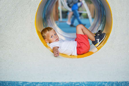 A little boy enjoys the underground multicolored tube on the playground on a sunny summer day. Standard-Bild