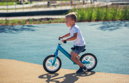 A little boy enjoys a balance bike on a playground in a park on a summer sunny day.