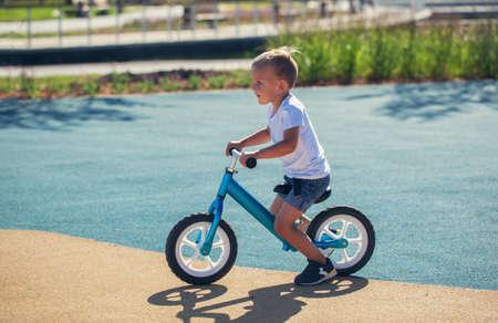 A little boy enjoys a balance bike on a playground in a park on a summer sunny day.