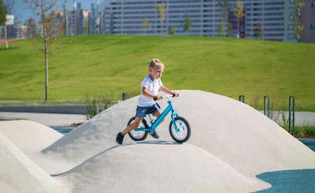 A little boy enjoys a balance bike on artificial hills on a playground in a park on a summer sunny day. Standard-Bild - 151236952