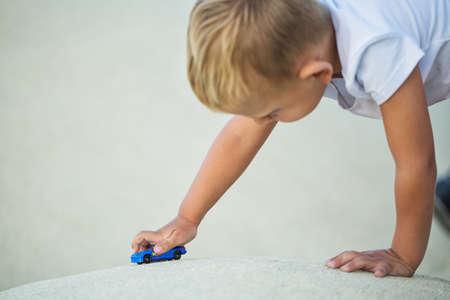 A little boy plays a sports car model on the playground 版權商用圖片
