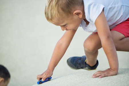 A little boy plays a sports car model on the playground Standard-Bild