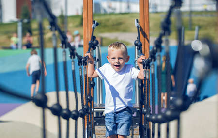 A little boy plays on a suspended rope bridge on the playground in the park on a sunny summer day.
