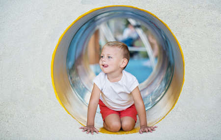 A little boy enjoys the underground multicolored tube on the playground on a sunny summer day. 版權商用圖片