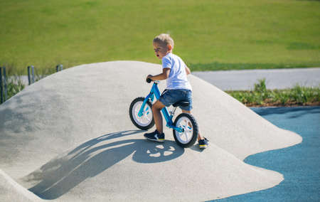 A little boy enjoys a balance bike on artificial hills on a playground in a park on a summer sunny day. 版權商用圖片