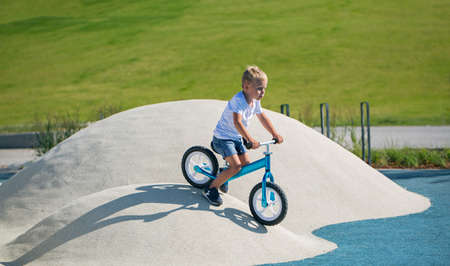 A little boy enjoys a balance bike on artificial hills on a playground in a park on a summer sunny day. Standard-Bild