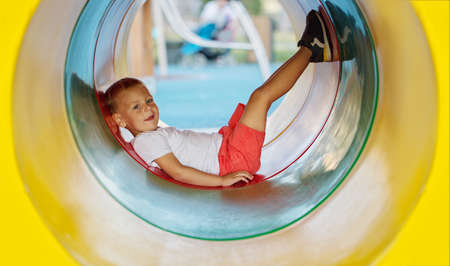 A little boy enjoys the underground multicolored tube on the playground on a sunny summer day.