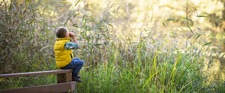 Little boy with binoculars sitting on a wooden fence in the reeds on the lake and exploring the environment warm autumn day. Wide large panorama