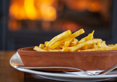 Clay oval plate of french fries on a wooden table, in a cafe on the background of the fireplace