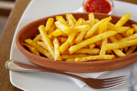 Oval clay plate of french fries on a wooden table, top view Banco de Imagens