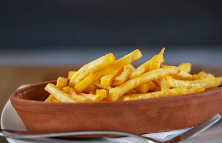 Oval clay plate of french fries on a wooden table,  front view