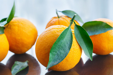 A pile of fresh ripe oranges with leaves from the garden on a glass table, close-up studio shot Imagens