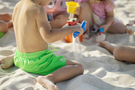 Children playing on the beach in the sand on a sunny day Stock Photo