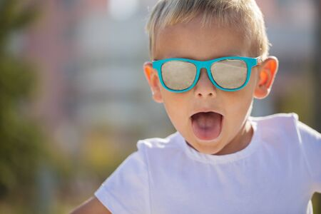 Handsome little boy in stylish sunglasses rides a scooter on a track in the park on a sunny summer day