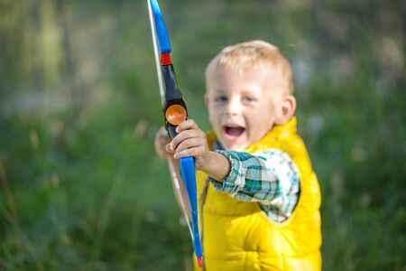 The young boy in the forest aims at the camera with a bow