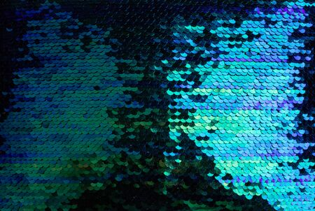 Background of green, blue and purple sequins close-up macro