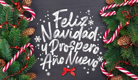 "Christmas card with wishes words in Spanish ""Merry Christmas and a happy new year!"" (Feliz navidad y prospero año nuevo). Christmas tree branch decorated with garlands, cones and caramel sticks on a black wooden table background, top view"