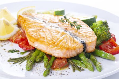 Grilled salmon steak butterfly with vegetables and asparagus on a white plate Archivio Fotografico