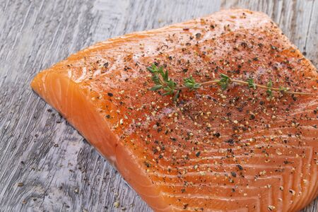 Nayad Scandinavian style fresh salmon filet covered pepper mix on a wooden board