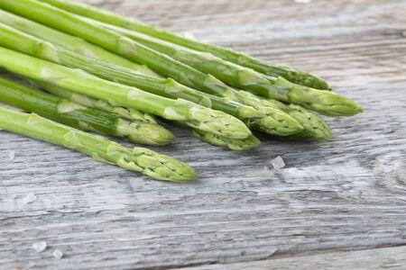 Bunch of fresh green asparagus on a wooden background Standard-Bild